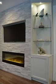 Fireplace TV combo - One end of fireplace wall with custom cabinetry, Erthcoverings Silver Fox stone, and Dimplex electric fireplace. Design by Stylish Fireplaces. Reface Fireplace, Tv Above Fireplace, Home Fireplace, Fireplace Remodel, Living Room With Fireplace, Fireplace Surrounds, Fireplace Design, Living Room Decor, Fireplace Ideas