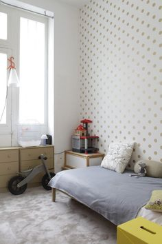 Boy room with golden dots on the wall, and nice color pallet of furniture and accessories.