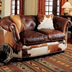 """BackOverviewShower your family and friends with some good old Southern hospitality and invite them to kick back and relax in the comfort of this luxurious King Ranch brown leather tufted loveseat. Eight-way hand-tied hardwood maple construction with brindle hair on hide, tufted leather seat back, and antiqued brass nailhead trim. Includes a pair of 18"""" brindle throw pillows. Please allow 12-14 weeks for delivery. 81""""w x 39""""d x 33½""""h. Made in USA. Note: Due to differences in dye lots…"""