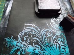 Apply Distress ink, stamp w/ versamark and emboss with clear embossing powder, cover it with black paint, then wipe the black away