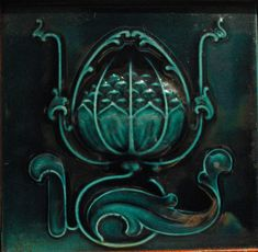 This beautiful Art Nouveau majollica tile appears on a side panel of an ornate Edwardian mahogany hallstand. The irridescent tile features a wonderfully stylised depiction of a water lily. Private collection.