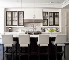 marble counter-tops, black cabinet details and gray bar-stools (vinyl?) // Jennifer Worts Design