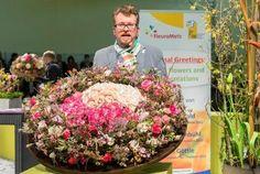 Stefan Göttle, Deutschlands Vizemeister der Floristen aus Baden-Württemberg, zeigt einen überdimensionalen Kranz aus Rosen. Das Yin und Yang-Motiv ist darin aus exklusiven Avalanche-Rosen eingearbeitet.