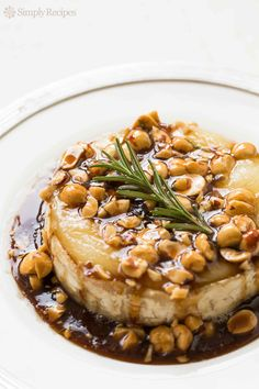 Festive Baked Brie! Drizzled with a sweet and sour honey sauce and toasted hazelnuts.