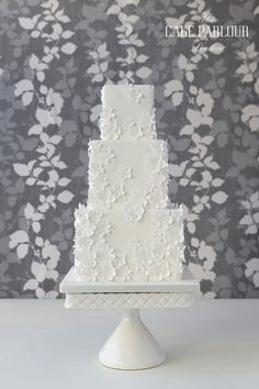 'FLORAL WHITES' Wedding Cake - Hundreds of small white iced and wafer paper flowers surrounding a deep tier cake.