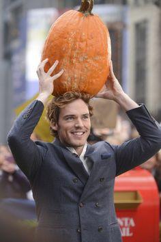 Sam Claflin holding a gigantic pumpkin
