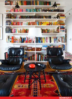 Pair of well-loved Eames loungers and ottomans in front of a wall of books. I would use a different rug and table....
