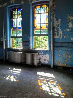 Patient sunporch in an abandoned hospital in NY; stained glass windows and a radiator