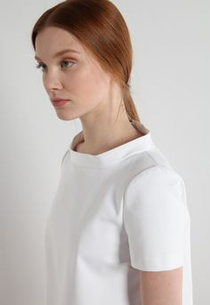 Stretch cotton top with wide rounded neckline. Short sleeve and button closure on back. The straight and basic line falls softly on the hips for a sporty chic look.