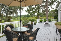 Enjoy dining al fresco on the deck of this gorgeous home with views of the Masonboro Country Club golf course and pond