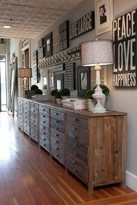 distressed reclaimed wood dressers white vintage lamps subway signs eclectic art gallery gray walls topiaries love the ceiling tiles