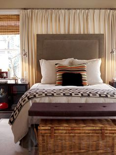 Hang curtains on an entire wall to provide a quiet sleeping room and to cover windows that a bedstead may partially cover.