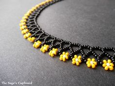 This adorable floral collar features a bumblebee inspired palette of yellow on black. The necklace is woven with a simple variation of chevron chain stitch for a light and delicate collar. The collar'