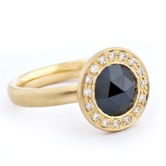 A contemporary 18k yellow gold satin finish engagement ring with one 8mm round rose cut black diamond center stone surrounded by a 16 round white diamond halo. By Anne Sportun