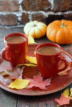 Two cups coffee with pumpkins and leaves