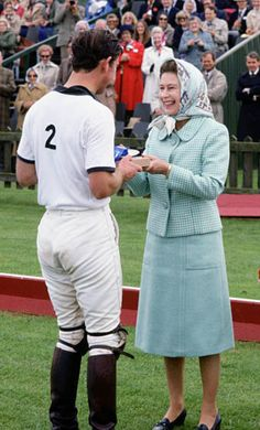 Queen Elizabeth II presents her son Prince Charles with a prize after a game of polo at Smith's Lawn, Windsor. (Exact day date not certain). (Photo by Tim Graham/Getty Images)