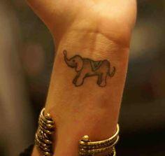 Tiny elephant tattoo on wrist.