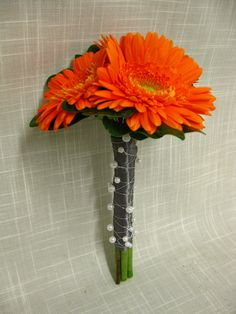 Orange gerbera daisy bridesmaid bouquet accented with a platinum satin wrap and white pearls.