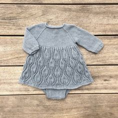 Tiny Tulips is a special one-piece for baby girls: a three-quarter-length sleeve romper with simple-cable hem and cuffs, and a full lace skirt with a pattern inspired of springtime budding tulips. Knit Baby Dress, Knitted Baby Clothes, Knitted Romper, Knitting For Kids, Baby Knitting Patterns, Baby Patterns, Baby Barn, Tulip Dress, Baby Sweaters