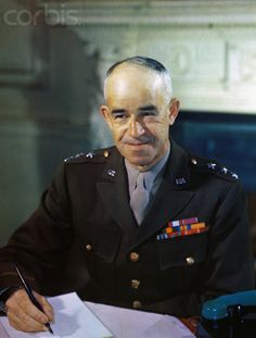 Lt. General Omar Bradley who commanded the 12th Army Group during World War II, smiles while seated at desk. 1944.