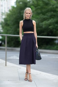 Kate Davidson Hudson in black cropped high collar tee, navy pleaded calf length skirt, strapped heels. Simplistic and cool.