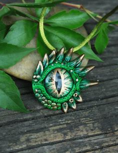A green dragon eye pendant made out of effect polymer clay, it has a glittering effect. For the finishing touches I painted it with acrylic paint, and lacquer. Its eyes are made out of glass, also painted by me. Comes with a green silk cord. Size: ~ 4,3 x 4 cm * It has 4 siblings in my shop (5th pic) :) ____________________________________________ Thank You for checking out my work! :) If You are interested you can see more at: https://www.etsy.com/shop/GloriosaArt an...