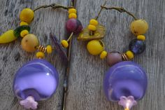 """Créoles asymétriques """" En mauve sous le soleil"""" avec graines Lumbang violettes, chips coco, fleurs Lucite, graines açaî, : Boucles d'oreille par les-perles-de-eihpos"""