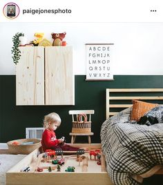 dark green accent wall in kids bedroom, floating cupboard unit