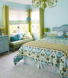 curtains = brown  walls = green  bedding = black, orange, green, brown, cream  pillows = combination  light =orange  dresser = black