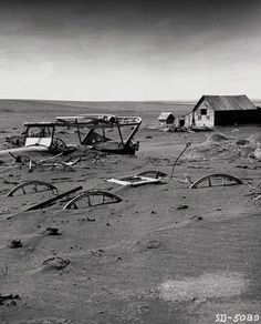 A farm is buried during the dust bowl years, early 1930s.: