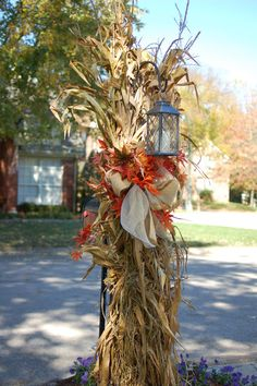 Fall outside decoration.  Corn stalk over the shepard's hook with a lantern.