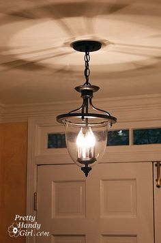 A New/Old Foyer Light - brass fixture spray-painted with oil-rubbed bronze. Love this idea!