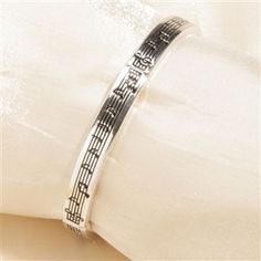 This stretchy and comfortable bracelet is a subtle way of showing off your love for music. Dress up for a night at the symphony or dress down for a relaxing concert in the park. The silver band is embossed with sheet music design and fits most wrists.