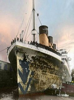 """RMS Olympic either during or shortly after wartime service, as evidenced by the remains of the """"Dazzle"""" camouflage on the bow."""