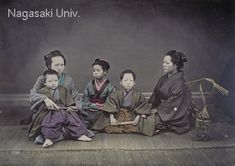 """The boys are probably brothers with their older sister. They wear """"haori"""" coats and """"hakama"""" trousers. The woman holding the younger brother on her knees is probably the mother and the woman on the right her mother-in-law. A woven bamboo basket containing rice cakes or perhaps """"chimaki"""" dumplings is nearby. This is probably a photograph to commemorate a Meiji Period """"Shichi-go-san"""" children's day festival, because the padded clothing indicate early winter. About 1880's, by USUI Shuzaburo"""
