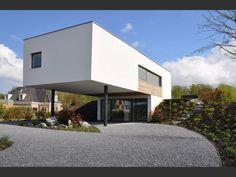 De woning is geïntegreerd in een bestaande heuvel met een rotonde als entree onder een overstek.