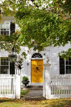Halloween Decor - decorate your front door & entry with black spiders! Love the contrast of the white picket fence & white house with that bright yellow front door! Look at that fanlight above the door! Beautiful Fall weather and autumn colors! New England Fall, New England Style, New England Homes, Fall Door Decorations, Easy Halloween Decorations, Spider Decorations, Halloween Designs, Fall Halloween, Happy Halloween