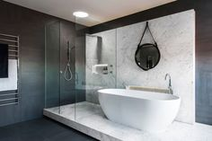 Minosa Design were asked to design a bathroom that would be modern, with a sharp edgy design, have a monochromatic color palette, and have a natural material as a feature.