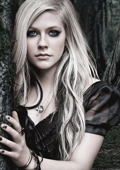 Avril Lavigne leaning closely to a tree.:).