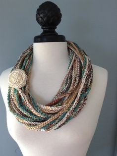 BLENDED TEXTURES AND COLORS....Single crocheted infinity necklace scarf in multi colors. Several different types of yarn and ribbons have been used to create a unique look. Can be worn in a variety of ways depending on the style you are going for. Wear it by itself, or dress it up with a decorative flower, button, or jewelry pin. The yarn and ribbon used is a blend of cotton, wool and acrylic . The scarf is approximately 46 inches around....long enough to wear it double or triple wrapped…