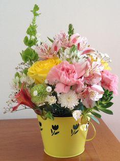 Flores2Home cubeta amarilla con variedad de flores, luce muy bien como centro de mesa o bien como regalo para alguien especial.