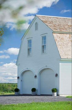 Arched garage doors on a white barn - very unique.