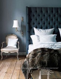 master bedroom with indigo walls, upohlstered headboard, white/nickel sconces
