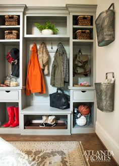 Transitional mudroom features gray built-ins filled with wicker baskets and backpacks flanking a built-in bench under a row of hooks alongside cubbies housing shoes and boots alongside metal wall baskets filled with magazine and books. Metal Wall Basket, Baskets On Wall, Wicker Baskets, Mudroom Laundry Room, Laundry Room Design, Halls, Atlanta Homes, Built Ins, Interior Design Living Room