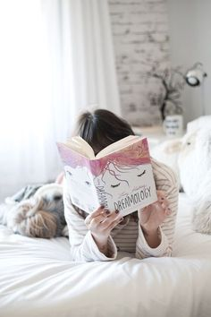 Resenha do livro Dreamology. Foto de Melina Souza. Mulher em cima da cama branca usando pijama listrado e lendo o livro Dreamology (young adult - jovem adulto) com o cachorro deitado do lado. Foto clean com predominância da cor branca.