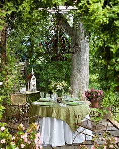 Small table and wrought iron chairs with hanging vintage chandelier in outdoor garden setting.
