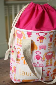 Use already made tote from craft store add printed fabric for cinch top. Makes a cute diaper tote for outings!