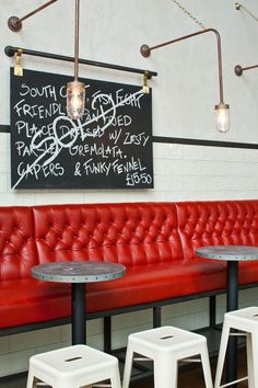 Jamie's Italian, London. Love the combination of these modern industrial elements - red leather, white tolix stools, exposed bulbs & chalkboard menu.
