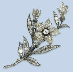 AN ANTIQUE DIAMOND BROOCH   Designed as a spray of flowers set throughout with cushion-shaped diamonds, a white paste stone at the centre, late 19th century, later rhodium plated