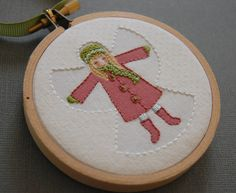 """This beautifully stitched design is by Corinne and it is for sale in her Etsy store 'SeptemberHouse' for $24.00 which is approx. £16.50. Size: 3"""" Christmas Holiday Ornament Embroidered Snow Angel in Pink and Green with a hanger loop of green ribbon secured with pink button. The ornament is beautifully boxed so it's easy to give as a gift. #embroidery"""